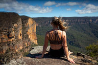 Woman relaxing on a cliff with scenic views