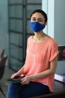 Mixed race woman wearing face mask in an office