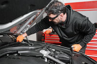 Auto mechanic working and repair on car engine in mechanics garage. Car service.