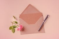 Invitation or greeting card mock-up, shot from above on a pastel pink background