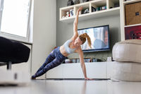 Attractive sporty woman working out at home, doing pilates exercise in front of television in her living room. Social distancing. Stay healthy and stay at home during corona virus pandemic