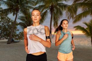 young women with earphones and smartphones running