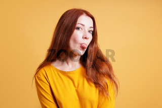 cheeky young woman sticking out tongue
