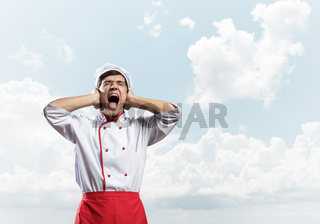 Young male chef screaming in shock and horror
