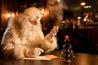 Thoughtful Santa Claus taking notes on paper