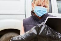 Lieferdienst Paketbotin mit Mundschutz überprüft Lieferung