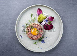 Gourmet tartar raw from beef fillet with yellow of the egg und vegetable as top view on modern design dish