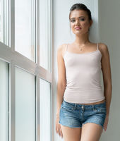 Slim brunette posing on window sill in studio