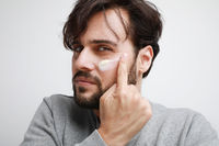 Bearded man applying moisturising his face. Grooming. Isolated on white wall.
