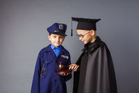 Children in costume of policeman and judge. Boys dream about future profession.