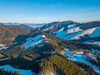 Winter Mountain Peaks and a Valley at a Ski Resort on a Sunny Day. Aerial View