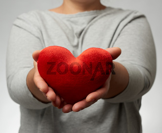 female hand holds a red textile heart