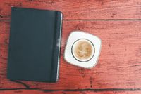 cup of espresso and diary on rustic red wooden table