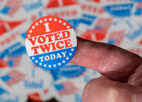Finger with I Voted Twice sticker in front of many election voting badges to illustrate voter fraud