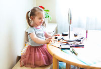 Adorable little child playing with cosmetics and doing makeup while looking in mirror