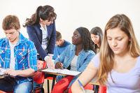 Lehrer hilft Schüler im Unterricht