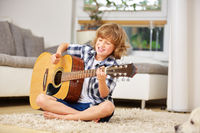 Junge lernt Gitarre spielen