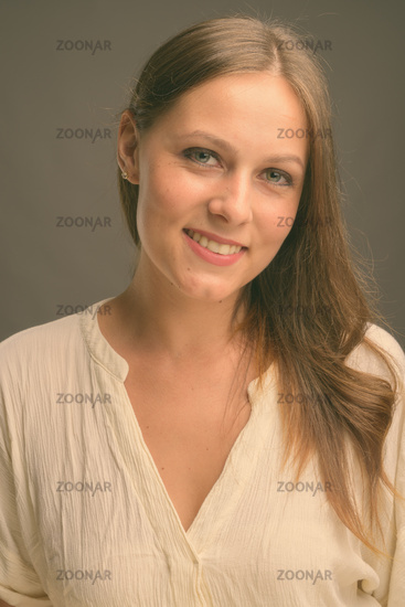 Portrait of young beautiful businesswoman against gray background