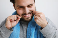 Close-up of attractive bearded man while flossing his teeth, grooming concept.
