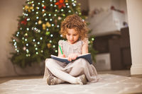 Preschool girl sitting next to festive tree and drawing
