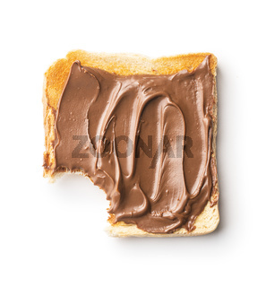 Bitten toast bread with hazelnut spread. Sweet chocolate cream.