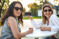 Cheerful adult women with coffee and mobile phone on street