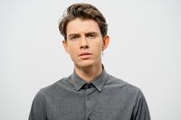 Young handsome man with a questioning face studio portrait. Boy style, trendy grey shirt look with cool hairstyle isolated on white background