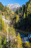 Autumn alpine Dolomites mountain view with small waterfall, Sudtirol, Italy