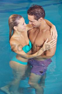 Paar im Wasser umarmt sich im Schwimmbad
