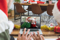 Rear view of man and son in santa hats waving while having a videocall with senior couple in santa h