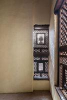 Corner of two Interleaved wooden ornate windows - Mashrabiya - in stone wall