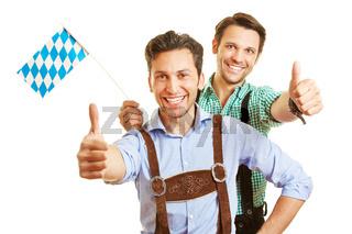 Zwei Männer halten Daumen hoch mit bayrischer Fahne