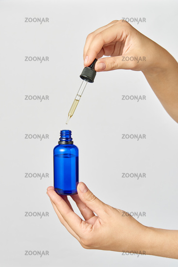 Female's hand holds a pipet of natural extract CBD oil against a light grey background.
