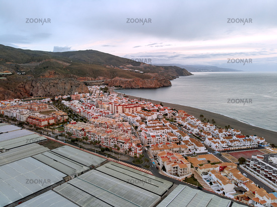 Aerial drone point of photo Calahonda small town in Andalusia. Greehouses and rooftops of residential buildings picturesque seaside calm Mediterranean Sea in the morning. Granada, southern Spain