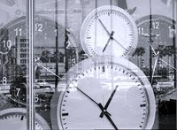 Large clocks reflecting in shop window illustrate the concept of time