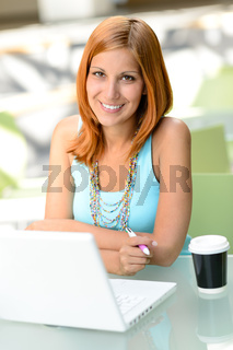 Smiling student girl sitting behind glass desk