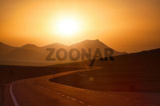 Auf der Kanarischen Insel Lanzarote führt diese Straße dem Sonnenuntergang entgegen zu den Vulkanen