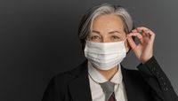 Pretty gray-haired middle-aged business woman putting on protective mask and showing ok or okey sign while posing on gray wall background. Quarantine concept