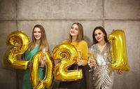Glamorous young females holding shiny golden balloon numbers 2021