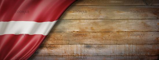 Latvian flag on vintage wood wall banner