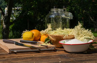 Ingredients for an elderflower liqueur on a wooden table in the garden