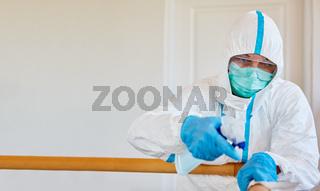Putzkraft in Schutzkleidung bei Desinfektion in Klinik