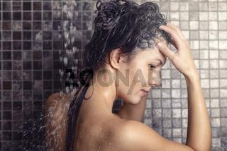 Frau massiert Shampoo in ihre Haare