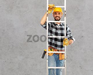 happy male builder in helmet climbing up ladder