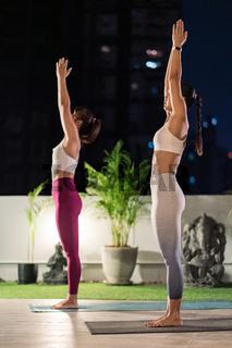 Asian women do yoga in city at night