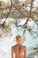 Rear view of topless beautiful woman wearing nothing but straw sun hat realaxing on wild coast of Adriatic sea on a beach in shade of pine tree.