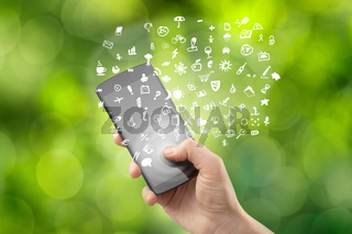 Hand holding smartphone with icons on green background
