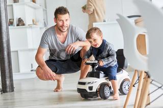 Kind fährt mit Rutschauto zu Hause als Kinderfahrzeug