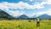 Hiker with Backpack standing on Hawkbit Flower meadow and View to panoramic Snow covered mountains with clouds and blue sky . Bavaria, Alps, Oberstdorf, Rubi, Allgau, Germany.