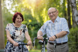Happy elderly couple with a bicycle. Handsome man and woman senior citizens. Husband and wife of old age for a walk.